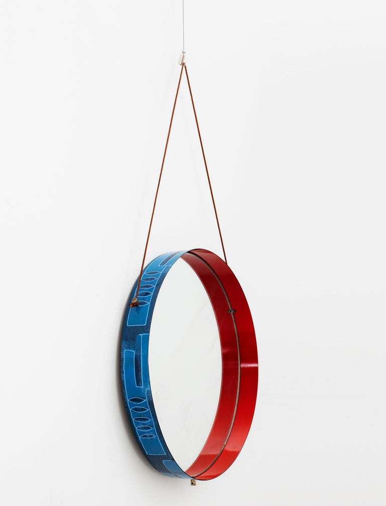Stunning Italian circular wall mirror in blue and red ceramic on metal frame by Siva Poggibonsi. Exterior of frame has painted shades of blue with leaf and geometric design. Interior is painted in a deep red lacquer. Amazing primary colors excite