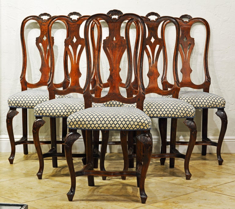 These late 18th century Italian Rococo or Louis XV style dining chairs feature beautifully curved back frames with small carved top arches, carved openwork splats, upholstered seats and carved cabriole legs united by low curved stretchers.