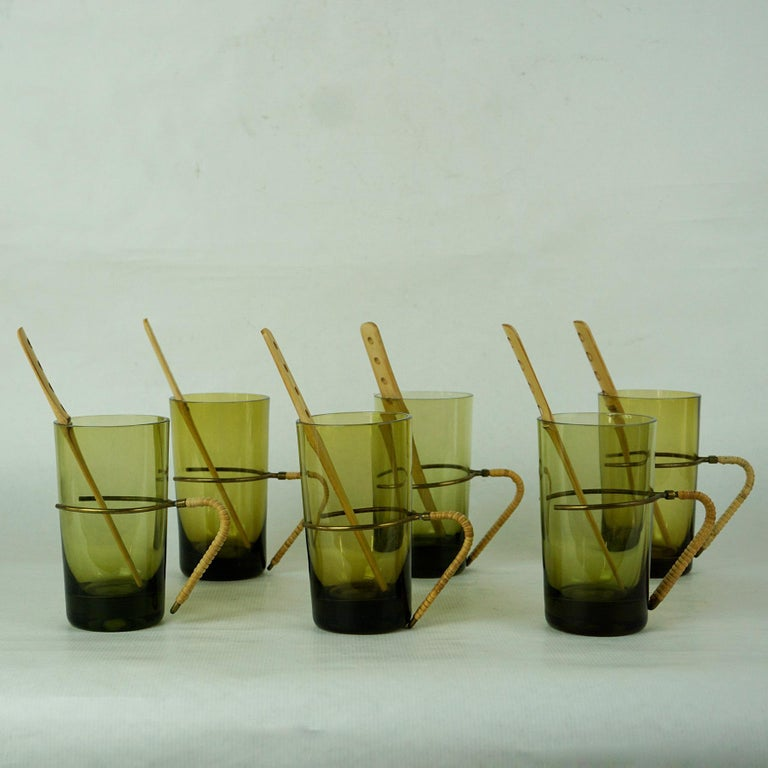Beautiful set of six green blown glass tumblers with bamboo stirrers and brass and wicker handles designed by Carl Auböck, Vienna, 1950s in excellent original condition. Carl Auböcks Designs love to combine materials like brass and wicker with