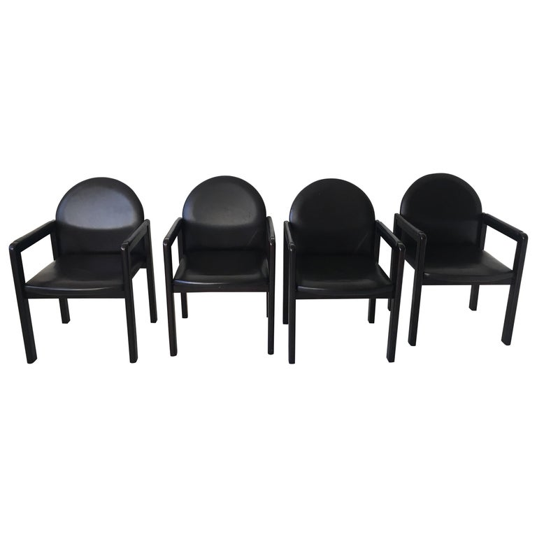 Six black leather armchairs manufactured by Bulo Belgium circa 1980s. The chairs feature a wooden base with Leather upholstery. They remain in a good and sturdy condition with some wear consistent with age and use like scratches to the wood and/or