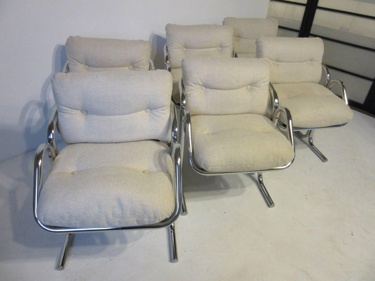A set of six tubular framed armchairs with oat meal toned upholstery and buttons, the cushioned seat and back are supported by a canvas sling design for greater comfort. With the lower arm profile they can be tucked under many table tops both dining