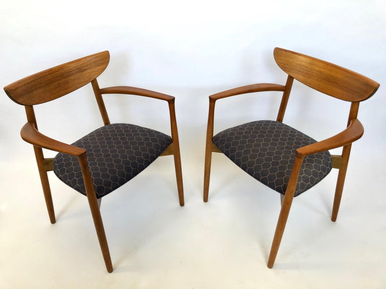 Set of six Harry Østergaard dining chairs in teak wood, comprises 2 captain chairs and 4 side chairs, all with original fabric and frames in very good-excellent vintage condition throughout. The chairs have curved back rests, tapered legs, and an