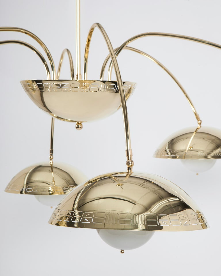 CHL3106  This large six dome chandelier in a hand polished solid brass finish has six staggered length arms extending from a central half dome body, the edge of which is adorned with Commune's signature