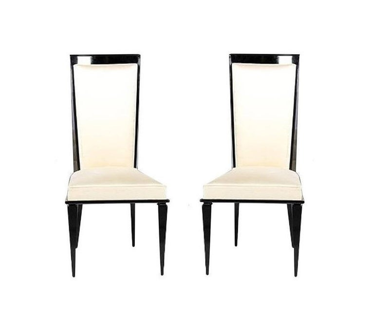 Elegant set of Art Deco dining chairs in the style of Maurice Jallot, Jules Leleu and Jean Pascaud. The chairs boast solid wood frames refinished in black lacquer with high backs and seats professionally reupholstered in a white cream color. They