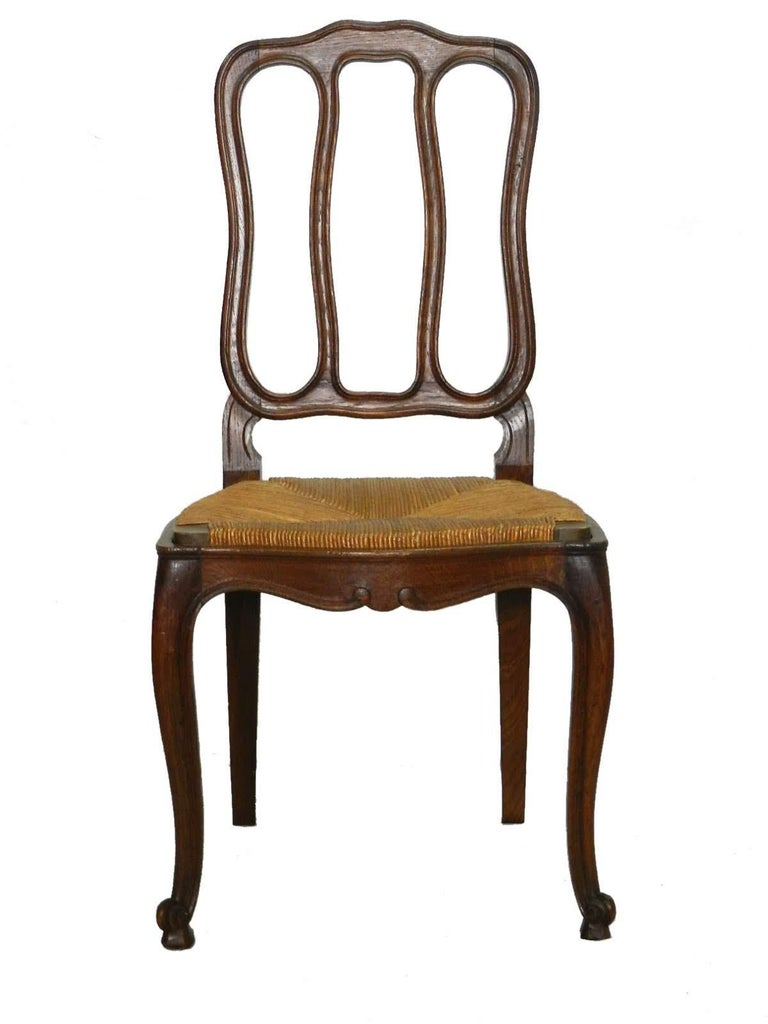 A charming set of six French Provincial oak chairs made in the 1940s. The rush seats are in excellent antique condition. The seats are removable and could be upholstered if preferred. The slight cabriole legs have carved escargot feet. A lovely