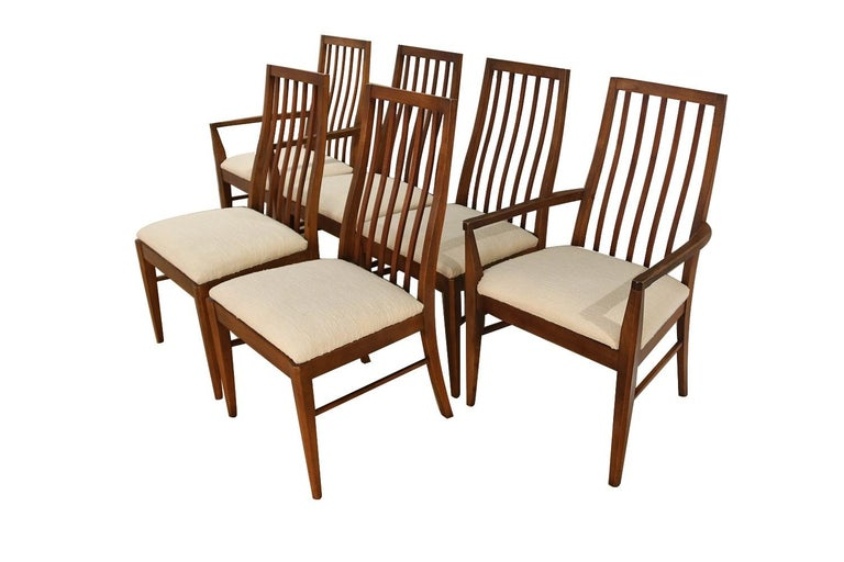 An absolutely stunning set of six Mid-Century Modern Lane First Edition dining chairs manufactured by Lane Furniture. These gorgeous chairs feature beautifully sculpted walnut frames with spindle curved backs providing lumbar support, making these