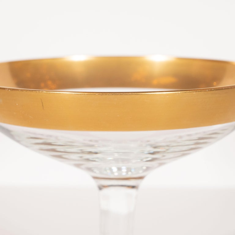 This elegant set of six champagne coupes were realized by the esteemed Mid-Century Modern designer, Dorothy Thorpe, circa 1945. They feature 24-karat gold rims- an exceptionally rare and sought after edition of this iconic glasses set-