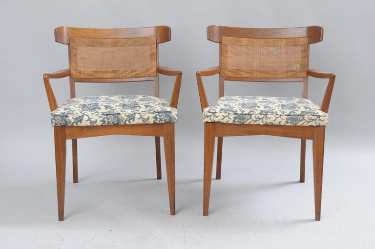 Set of six Mid-Century Modern walnut curved cane back dining chairs by Modern Manor Inc. Item features two armchairs, four side chairs, solid walnut wood construction, curved and caned backs, tapered legs, original label to underside. Style similar