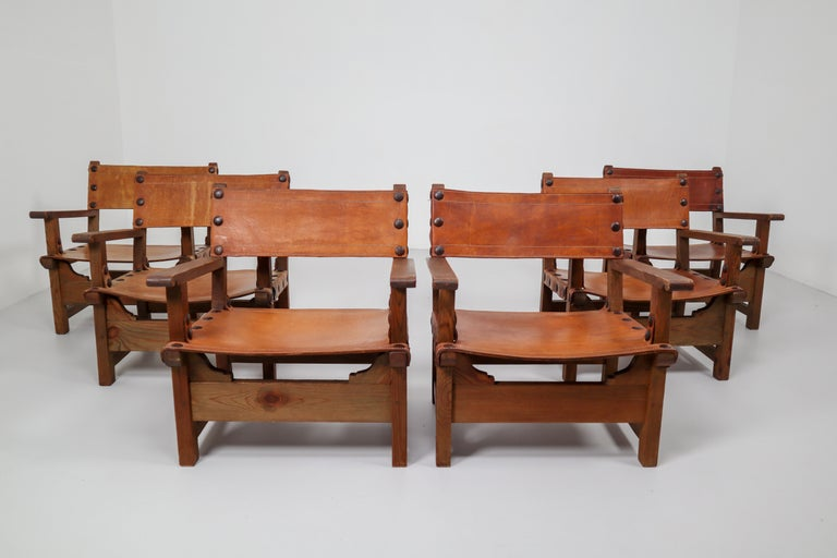 Set of six French morden lounge chairs in absolutely gorgeous patinated cognac saddle leather and solid pinewood, circa 1950s. The thick saddle leather is beautifully patinated during use and age and shows interesting stitching. There is a color