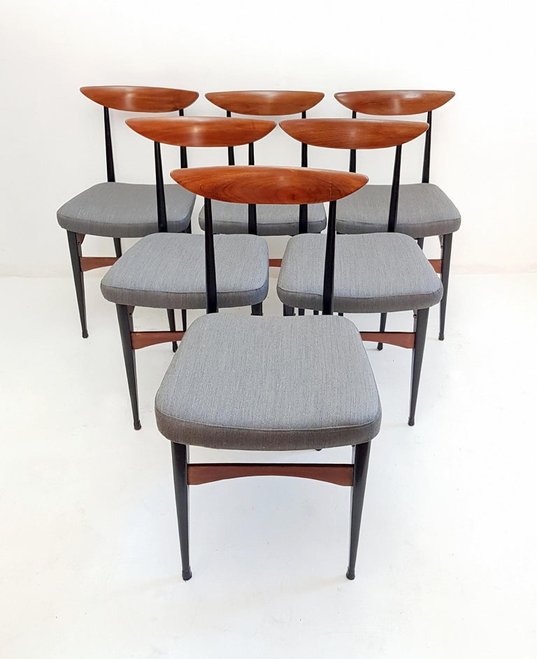 A set of six Italian dining chairs with a strict design in teak and blackened wood and reupholstered in gray Italian soft wool. The chairs are lightweight but very stabile and robust. The chairs have supreme craftsmanship and have recently been