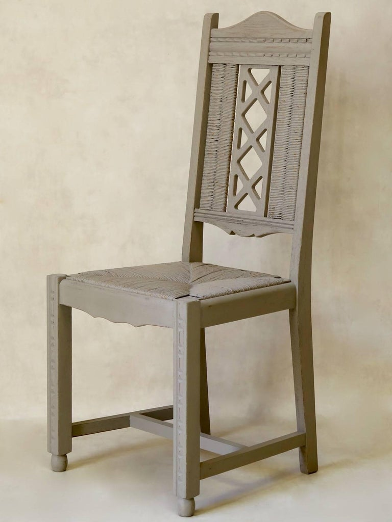 Set of six unusual oak dining chairs, with a geometric patterned design carved on the wood, and a criss-cross motif on the backs, flanked on either side by rush detailing. The front legs are raised on ovoid ball feet. The legs are joined by an