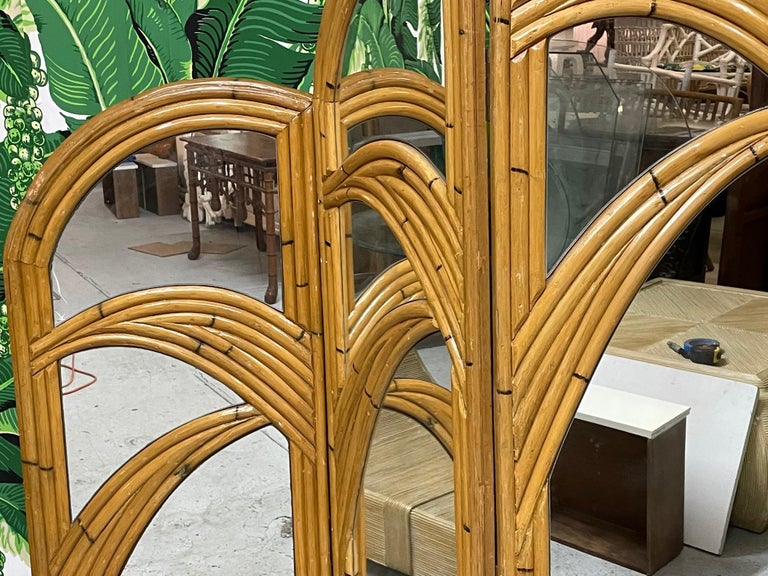 Pair of 3-panel room divider screens feature veneer of pencil reed rattan in a palm tree motif. Very good vintage condition with only minor imperfections consistent with age. Left screen is slightly lighter in color than right screen. Each panel
