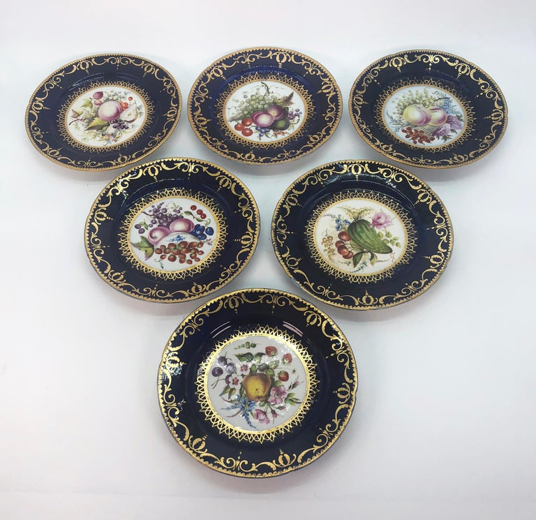 Six Regency side plates by Coalport with hand painted panels of fruit, circa 1805. Cobalt borders support a gilded band of interlocking scrolls and finials with a gold dentil border. Hand painted panels of fruit and flora in the manner of the