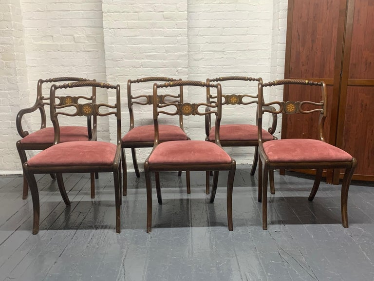 Six rosewood English Regency style dining room chairs. The seats are suede upholstery, have brass trimming and the back of the chairs has inlay pattern.   Armchairs measures: 34 H x 20.5 D x 21 W. Arm height 25.5 Without arms: 34.5 H x 21 W x 20