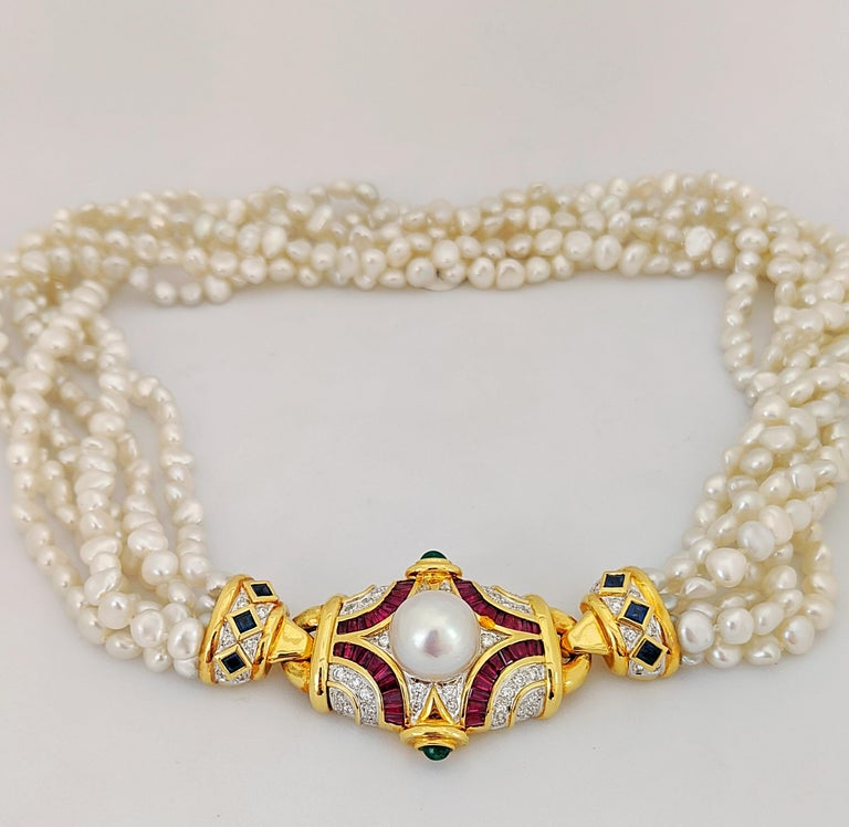 This exquisite necklace feature 18 karat yellow gold clasp set with round brilliant cut Diamonds and baguette cut Rubies. The piece is further accented with cabachon Emeralds and a 12.5 mm South Sea Pearl. The two end pieces are set with Diamonds
