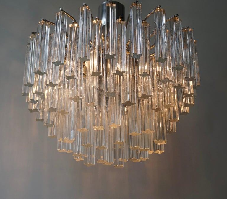 A very glamorous chandelier made up of graduating tiers of approximately 100 triangular clear glass crystals and with four light sources taking medium base bulbs. Measures: Diameter 47 cm. Height 48 cm.