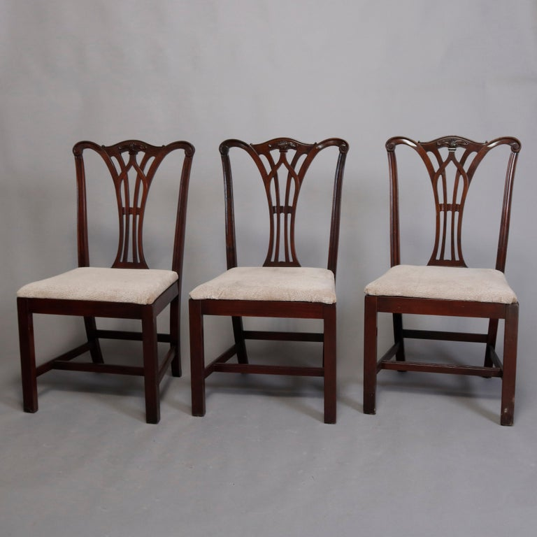 A vintage set of six Chippendale style dining chairs offers carved mahogany frames with ribbon backs having crests with carved foliate reserves and surmounting upholstered seats and raised on square and straight legs, circa 1930  ***DELIVERY NOTICE