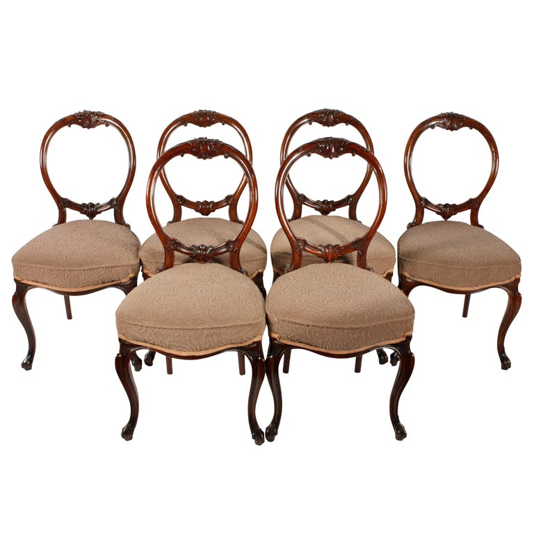 A fine set of six Victorian walnut cabriole leg chairs with a balloon back.
