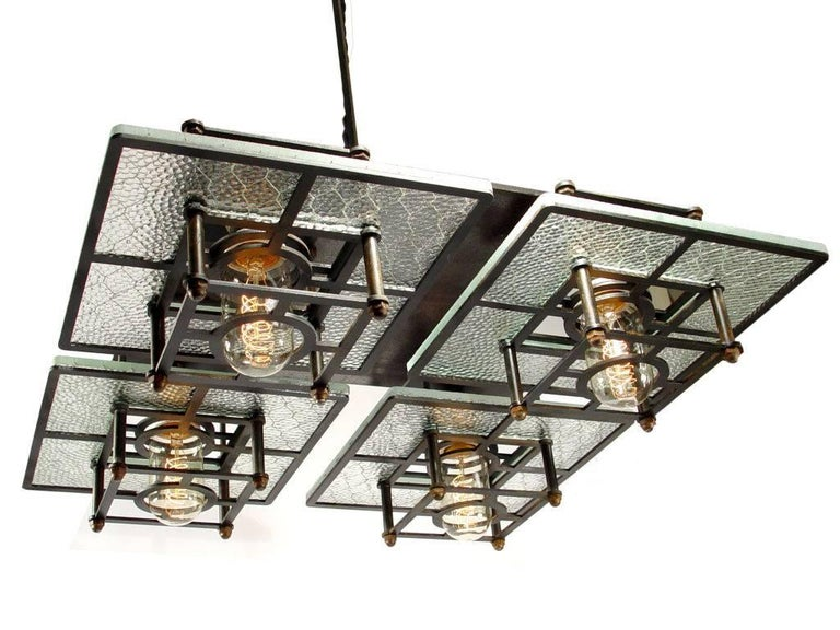 This impressive 19 inch square lamp features 80 year old pebbled wire glass contrasted by a custom made blackened steel frame. The esthetic fits perfectly as a transition between Industrial and modern styles. It has a Frank Lloyd Wright feel to it.