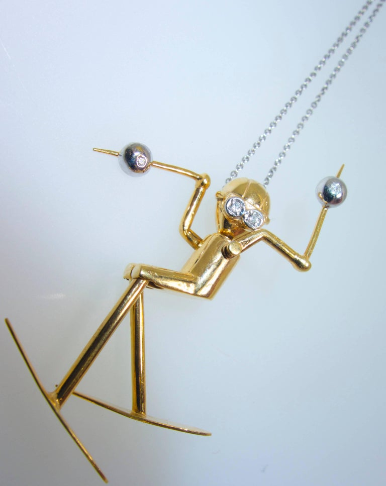 Skier hand made, all articulated so the joints move, this happy skier is in gold with accents of round white brilliant cut diamonds, 4 .  It is 1.5 inches long and marked 585 for 14K and with the maker's initials JJ.