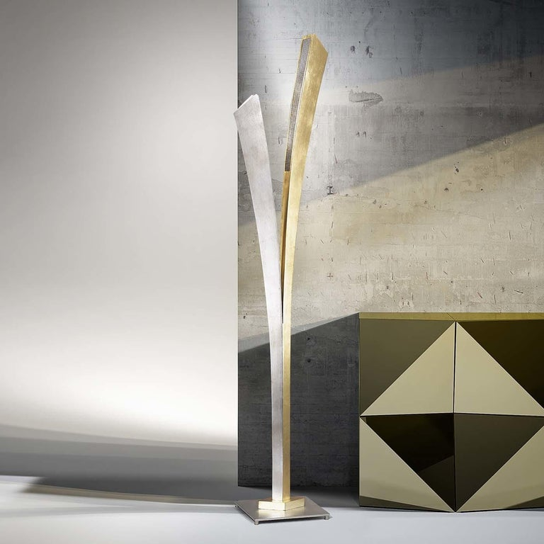 This handmade striking three-light floor lamp features a simple design adorned with two leaf-like metal elements, one with a gold leaf finish and another with a silver leaf finish. The effect is elegant and Minimalist at the same time.