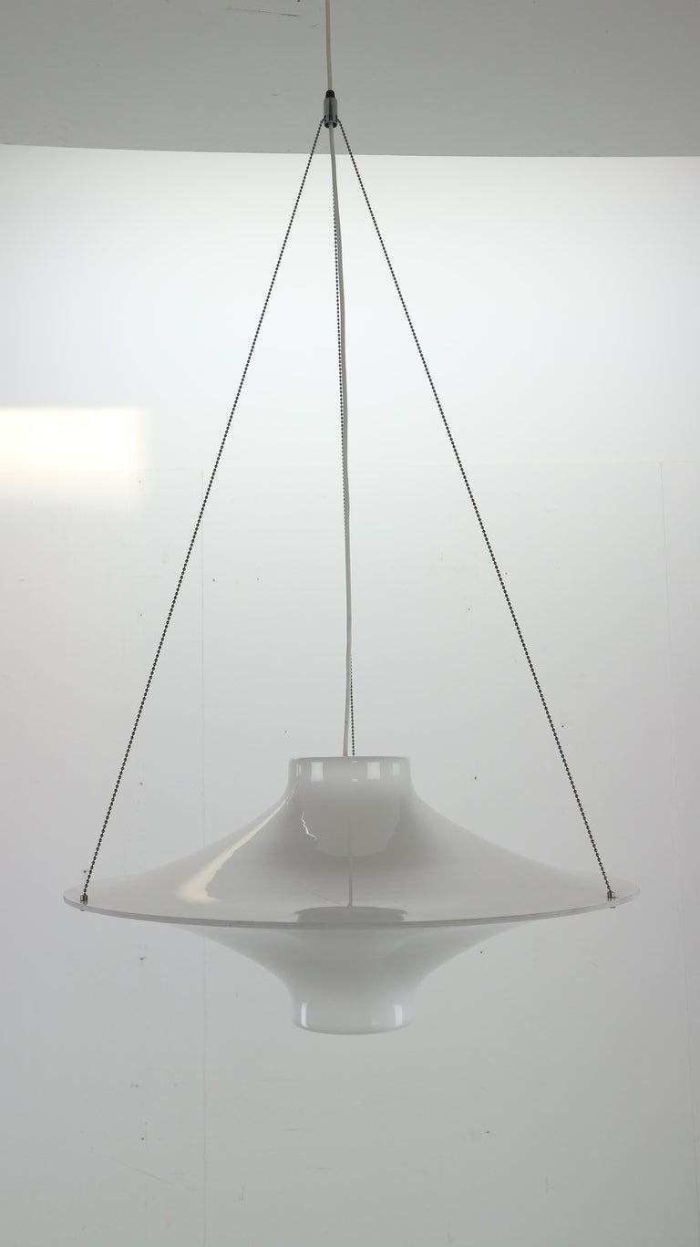 The 'Skyflyer' is designed by Yki Nummi in 1960. Yki Nummi was famous for his early use of acrylics in his designs. Skyflyer hanging lamp is comprised of two-piece shade made of molded opaque acrylic, and suspension chain. Thanks to the bulb