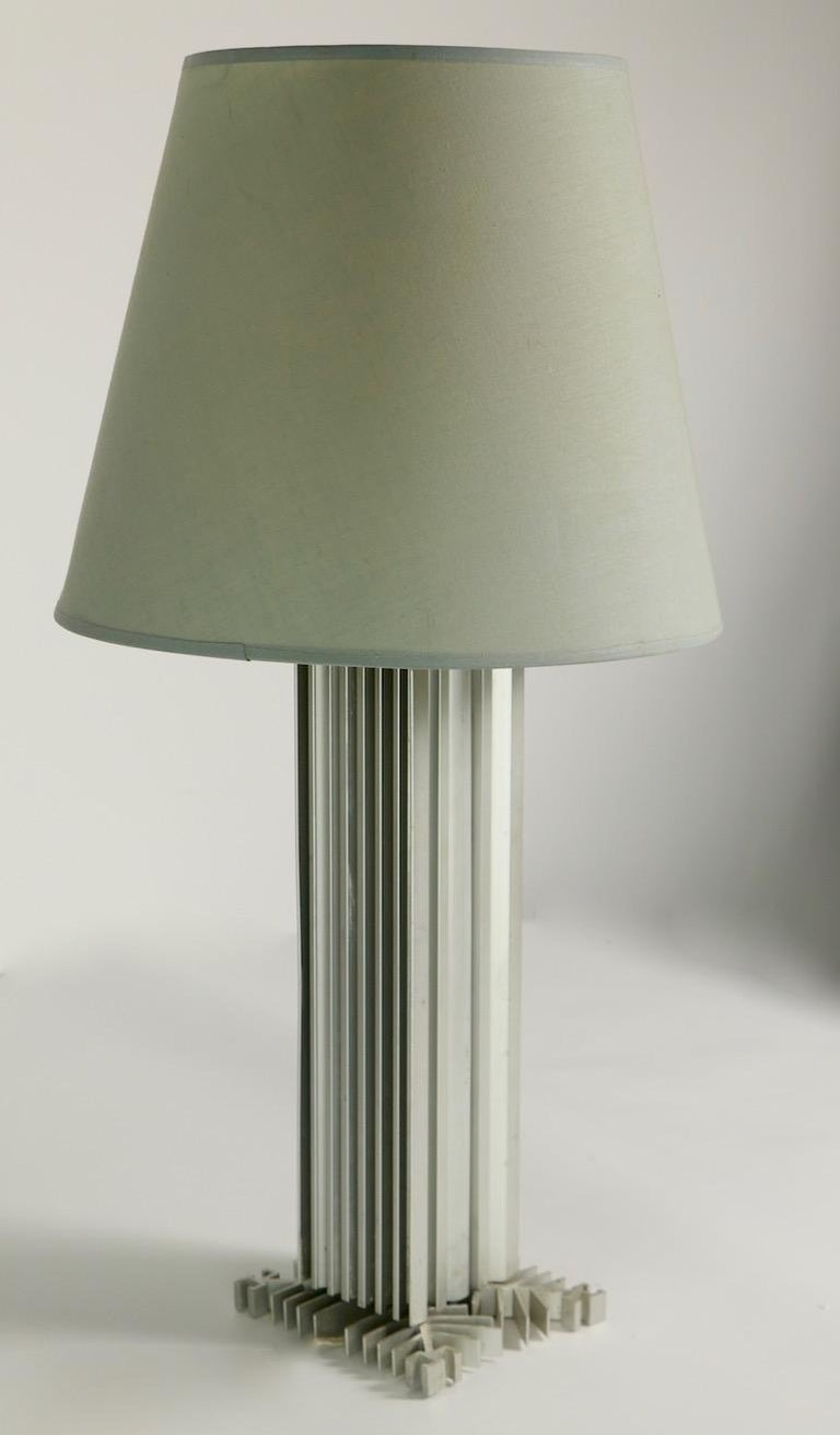 Modernist International style table lamp having a rectangular body on a sculpted square geometric base. Interesting form reminiscent of modern glass skin skyscrapers. The lamp is in original, clean and working condition, showing only light