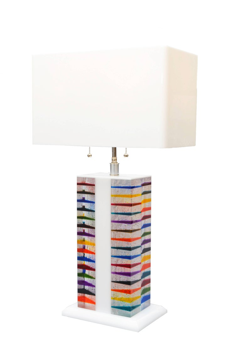 Architectural shaped table lamp in bright colors. Comes with a unique matching rectangular shade in Lucite. The lamp holder can support two lamps of max 60 W each and is of the highest quality. This lamp is new and can be ordered from stock or