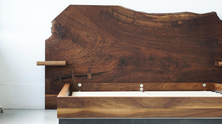 This modern queen bed headboard and frame is handcrafted from a solid claro walnut slab (headboard), black walnut (frame) and steel to create a blend of materials just as unique as the slab itself.   Features floating nightstands with stealth phone