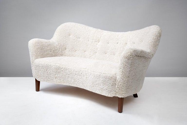 Slagelse Mobelvaerk  Model 185 sofa, 1952  Rarely seen curved loveseat sofa from Danish cabinetmakers Slagelse Mobelvaerk. Stained oak legs and new sheepskin upholstery from New Zealand.
