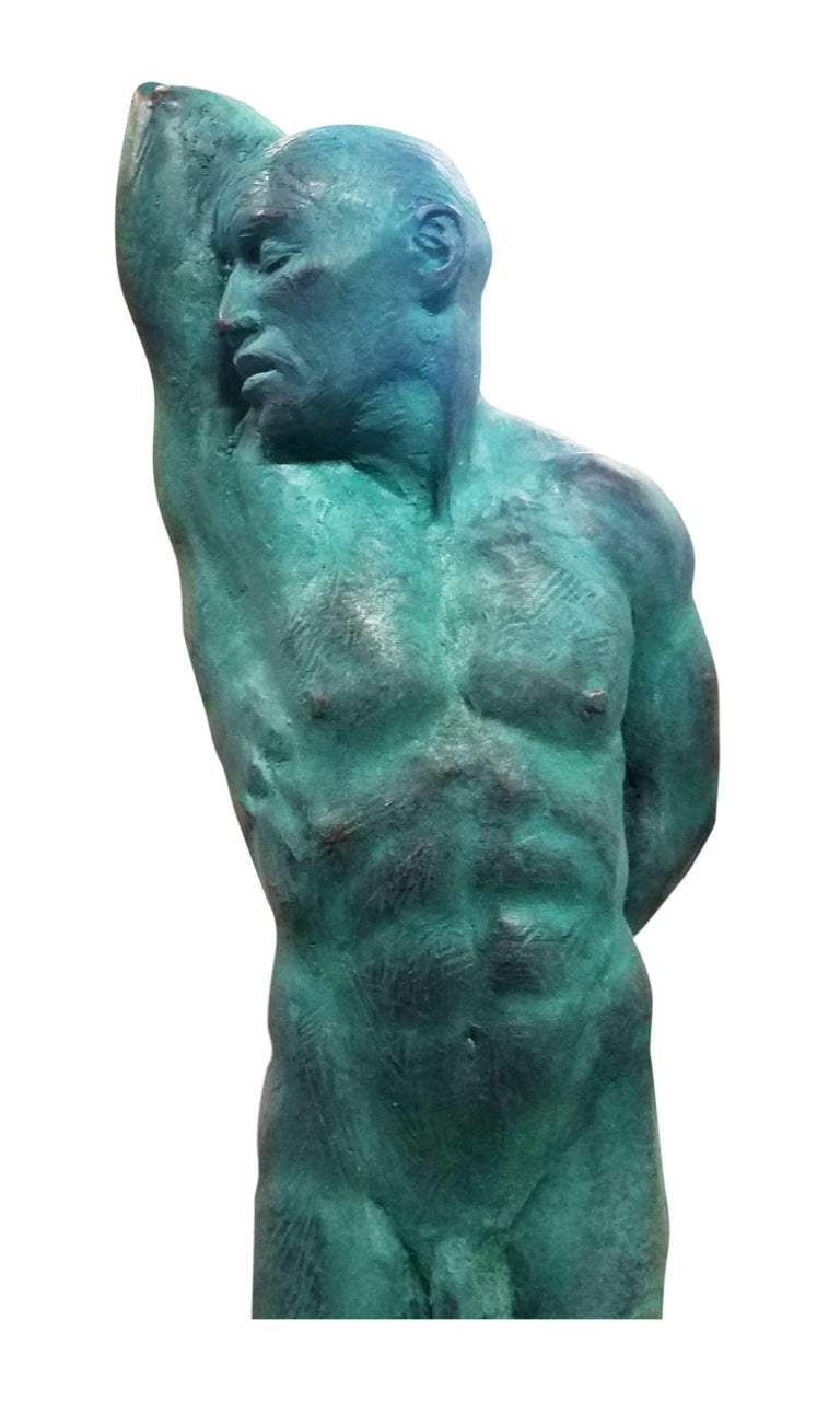 This is an extraordinary bronze sculpture of a Classic male nude by artist Dean Kugler. Attention to detail and complete understanding of the human figure are evident. The Slave stands with most of his weight on one foot and his arm stretched