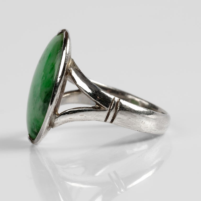 Featuring a large (18.3 x 12.3) oval cabochon of mottled, translucent green jade set within a brilliantly simple hand-made 14K white gold mounting, this late Art Deco-era (circa 1939) ring is a study of sleek simplicity. The highly polished jade