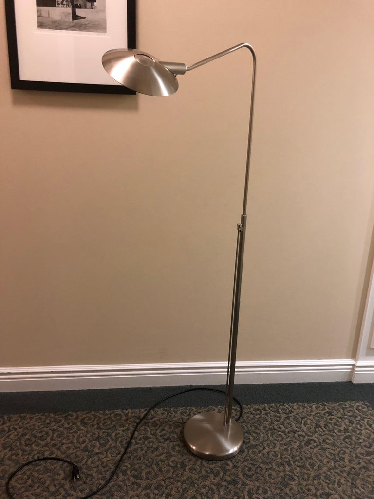 """Stylish modern reading floor lamp with swing arm offering both direct and indirect light. Uses 120V/200W halogen bulb. Finished in satin nickel. Shade can be tilted and angled.  Adjustable height is between 44""""and 54"""" from floor to top of shade."""