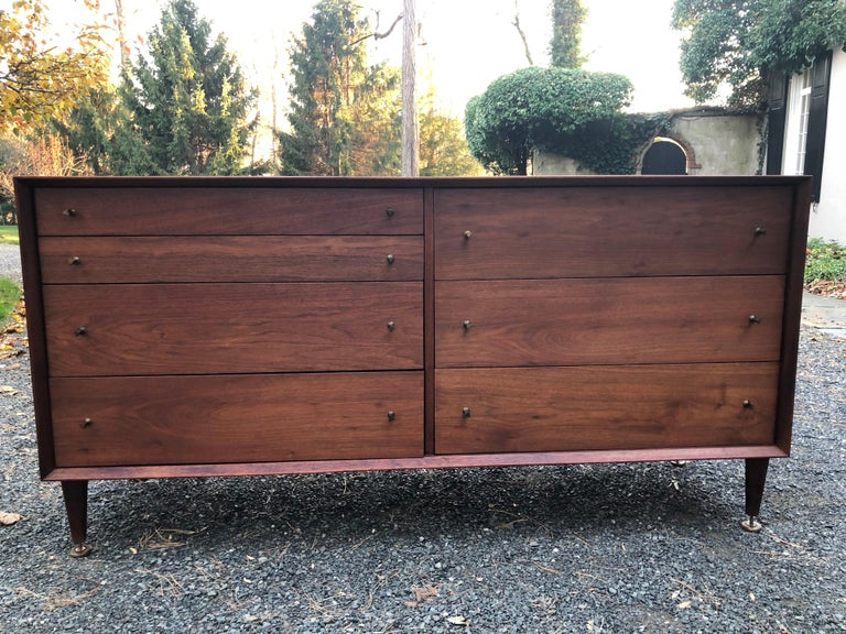 A handsome midcentury credenza dresser by renowned furniture maker Grosfeld House. Made of walnut, the credenza has a beveled frame front. The seven drawers each have metal triangular pulls and the edges of each drawer have a matte black finish. The