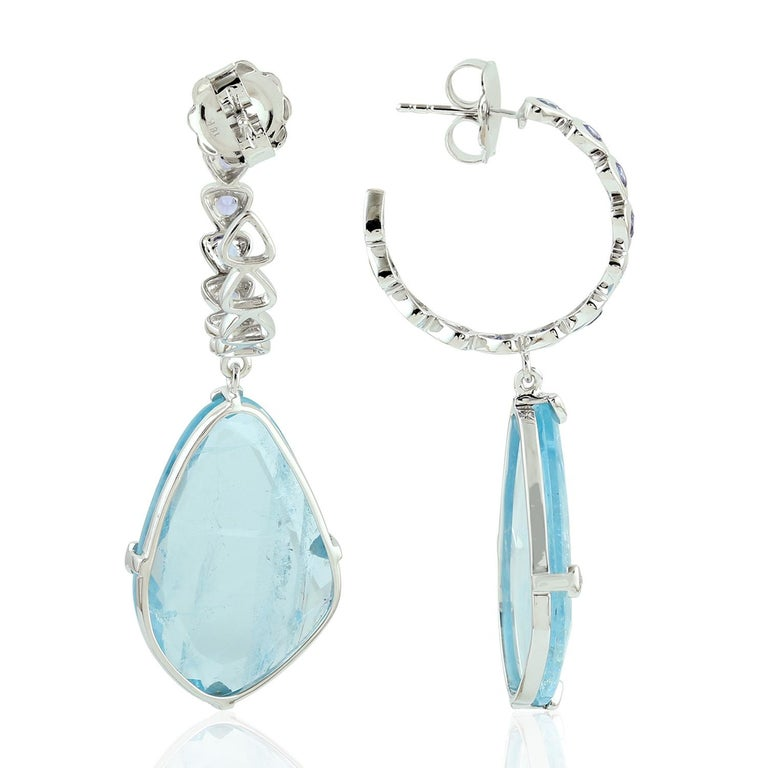 Sweet and sassy this sliced aquamarine earring with bezel set Tanzanite hoop on top is chic in 18K white gold.  Closure: Push Post  18KT: 9.394gms Diamond: 0.11cts AQUAMARINE: 25.60cts TANZANITE: 1.12cts