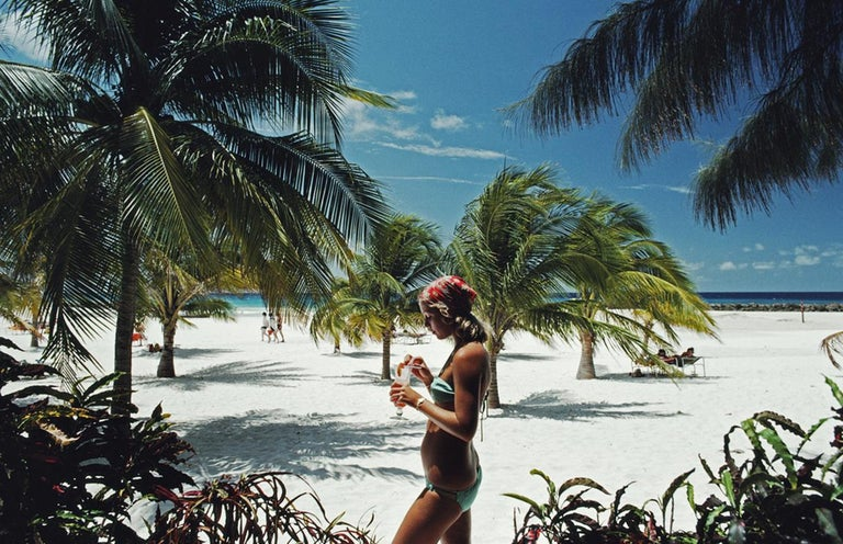 Slim Aarons Estate Edition - Barbados - Sarah Marson Williams Supersize 72 x 48 inches  print  Limited to 150 only   Sarah Marson Williams enjoys a cocktail on the beach at the Hilton Hotel, Needhams Point, Barbados, April 1976. (Photo by Slim
