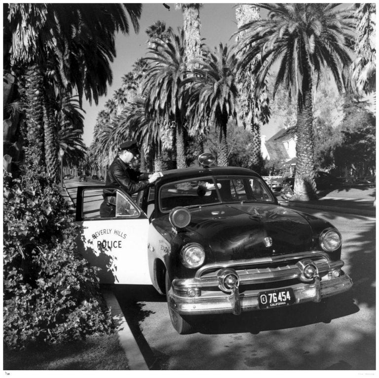 Slim Aarons - Beverly Hills Cop - Estate Stamped Edition  Limited to 150 only  American policeman Lee R Hathaway with his car on Bedford Drive in Beverly Hills, California, 1952. (Photo by Slim Aarons).   This photograph epitomises the travel style
