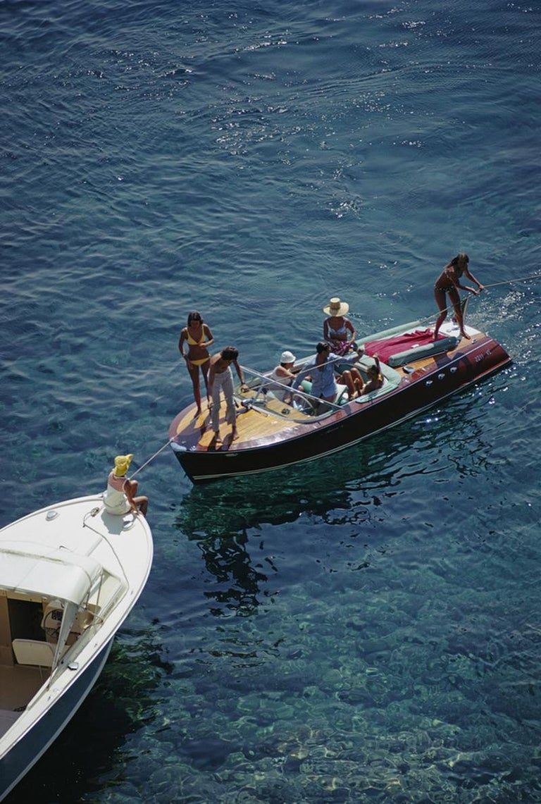 Boating in Porto Ercole, Italy, August 1969.   (Photo by Slim Aarons)  Estate Stamped Edition  Limited to 150 only   Unframed   This photograph epitomises the travel style and glamour of the period's wealthy and famous, beautifully documented by