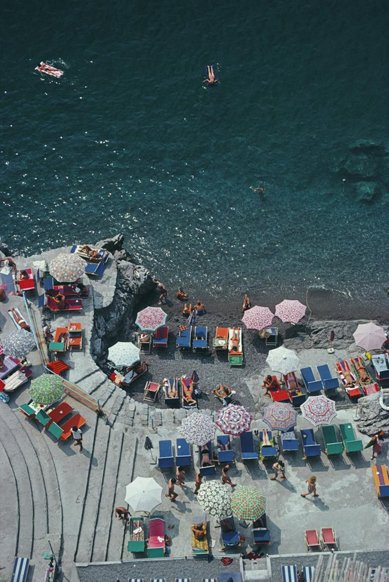 Slim Aarons Estate Edition - Positano Beach  Estate Stamped Edition  Limited to 150 only   Elevated view looking down on sunbathers and parasols on the beach at La Scogliera beach in Positano, Italy, 1979. (Photo by Slim Aarons).    This photograph