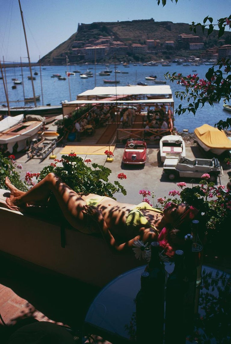 Slim Aarons Estate Edition - Sunbathing In Porto Ercole - Photograph by Slim Aarons