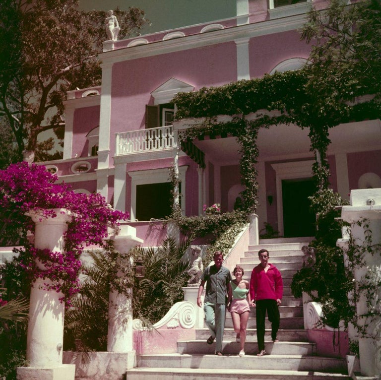 Slim Aarons - In Capri - Estate Stamped  Robert Hornstein, the artist Novella Parigini and Prince Dado Ruspoli on Capri, circa 1958. (Photo by Slim Aarons)  This photograph epitomises the travel style and glamour of the period's wealthy and famous,
