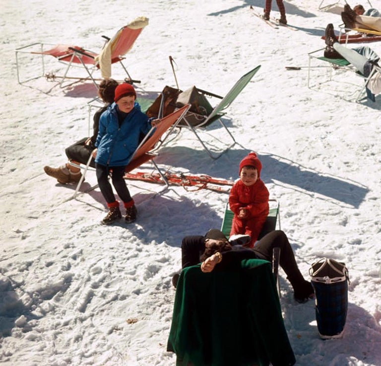 Verbier Vacation: Skiiers on holiday take in the sun on a snow-covered mountain top in Verbier, 1964. In one of Slim Aarons most popular and iconic images, bright, colorful notes of red, yellow, blue and green punctuate the clean white snow, with