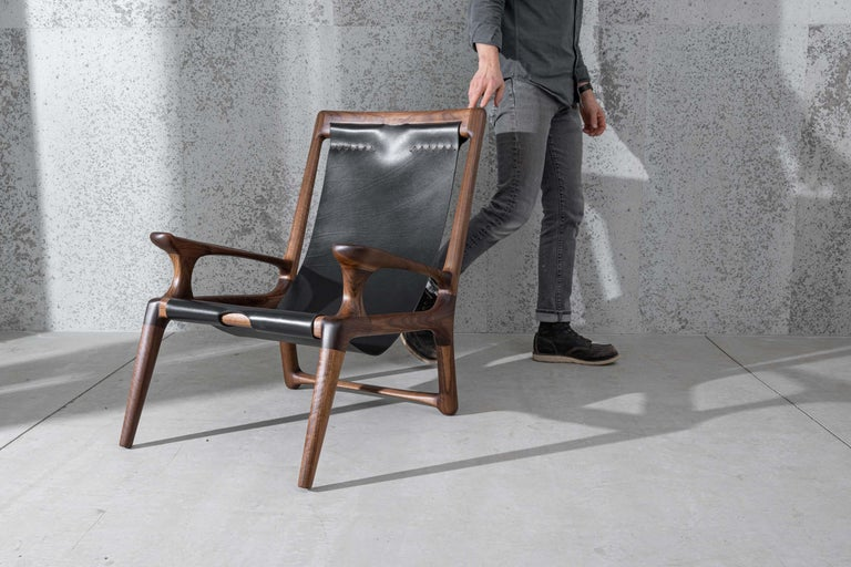 This chair is exactly the same as our Classic sling chair with one exception: the arms connect to the back supports. This listing includes one chair.  This award-winning leather and wood sling chair is the inaugural piece designed by Fernweh