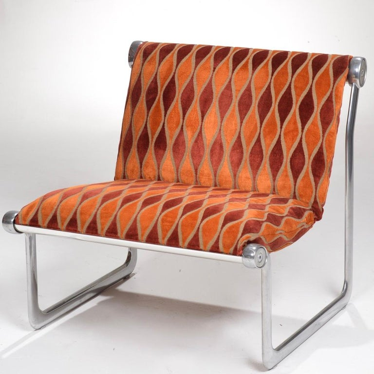 Sling lounge chair designed by Bruce Hannah and Andrew Morrison designed in 1971 for Knoll International. Sling seat upholstered in an orange biomorphic curve embossed velvet, on a polished aluminum frame.