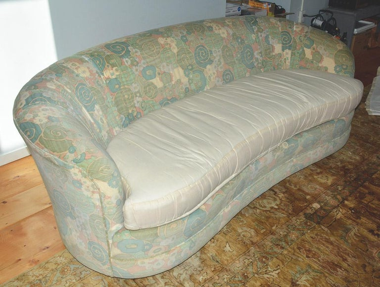Beautiful 1950s curved sofa with alluring low swung lines. Original velvet on sofa has yellowed and also lacking the cover for the seat cushion, Slip cover has some stain in the back. Sofa is ready for new upholstery or new slip cover at an