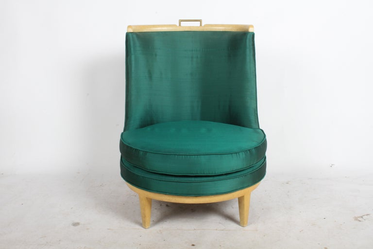 Mid-Century Modern low barrel back slipper chair in the style of Architect Samuel A. Marx. Has a faux finish similar to goat skin, with brass handle at top of chair. Shown in all original condition with original emerald green silk upholstery, seat