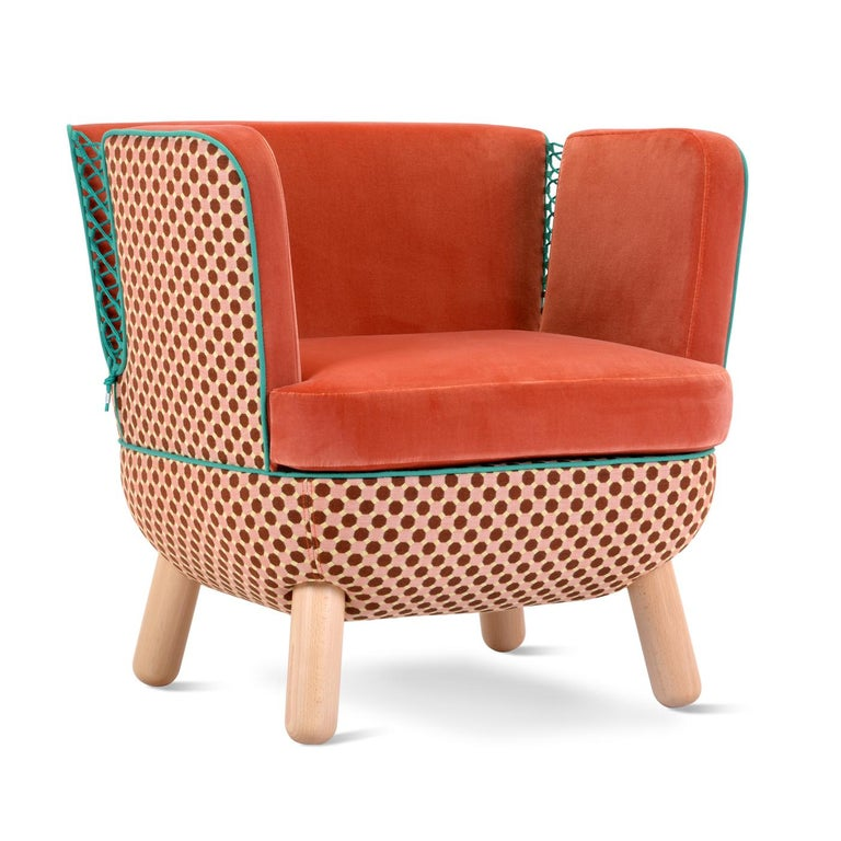 With its enveloping shape, this designer armchair is characterized by the slits on the back, which is available in a high or low version. The slits are closed with polypropylene cords in various colors. The legs shown here in natural beechwood are