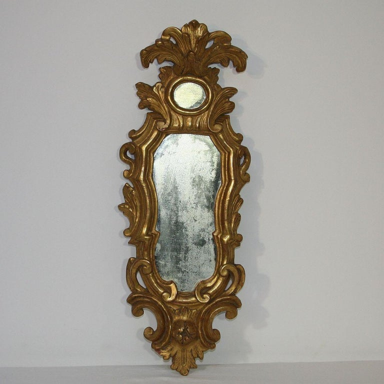 Stunning small baroque giltwood mirror, Italy, circa 1750. Weathered, small losses and old repairs. Traces of inactive woodworm.