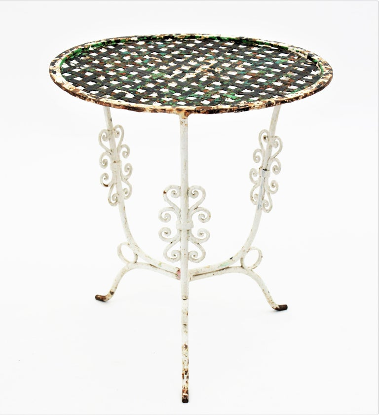 Lovely garden low round table with intricate iron top standing on a tripod base, France, 19th century. This small patio table has a terrific aged patina showing different coats of antique paints. It has scroll decoratif motives on the legs and an