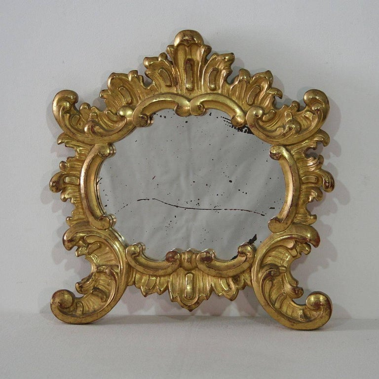 Well carved small giltwood Baroque style mirror. Gorgeous small piece, Italy, late 19th century. Weathered.